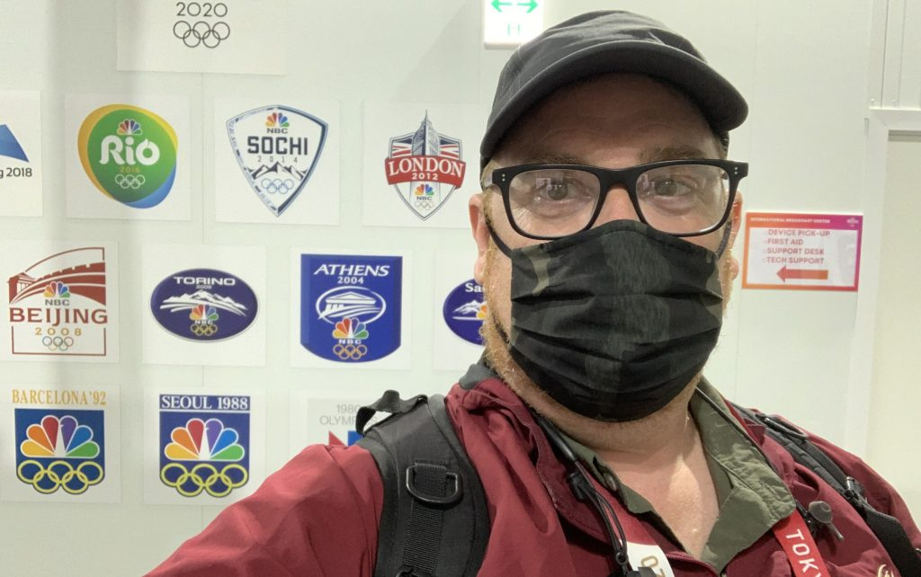 Photo of Max Negin in front of Olympics logos.