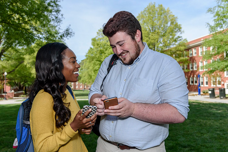 photo of a woman and man conversing together with their cellphones