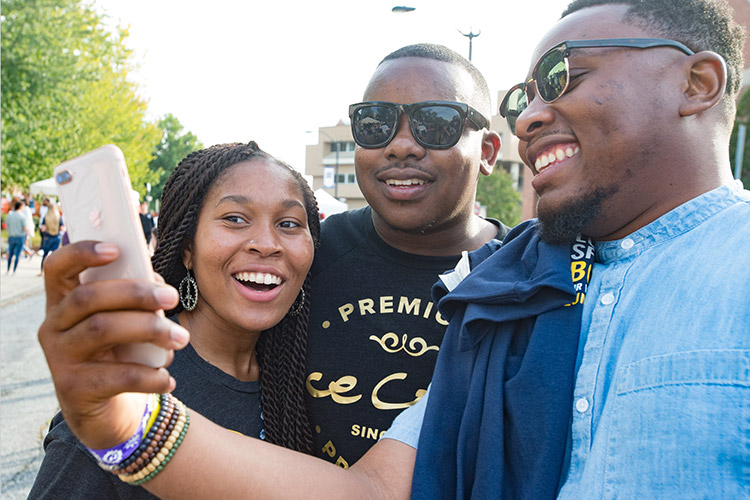 Three Spartans share a social media moment using a cell phone.