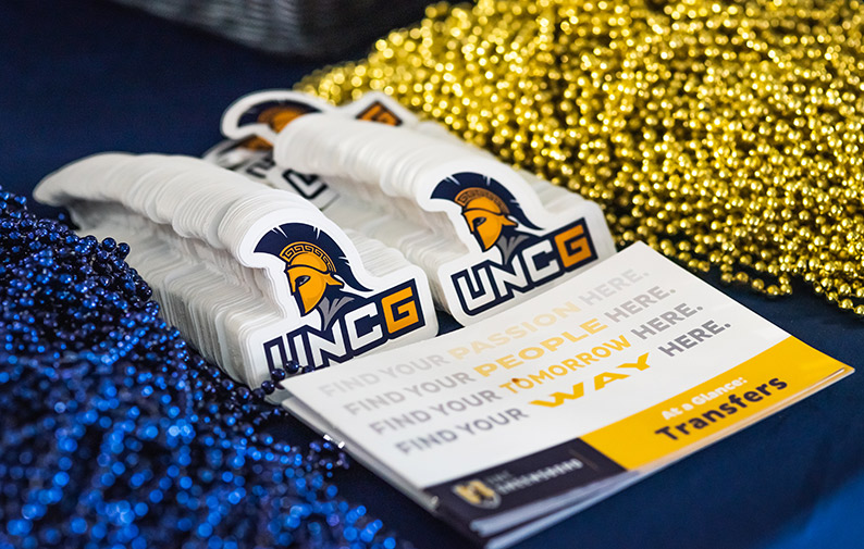display of UNCG swag, stickers, and beads