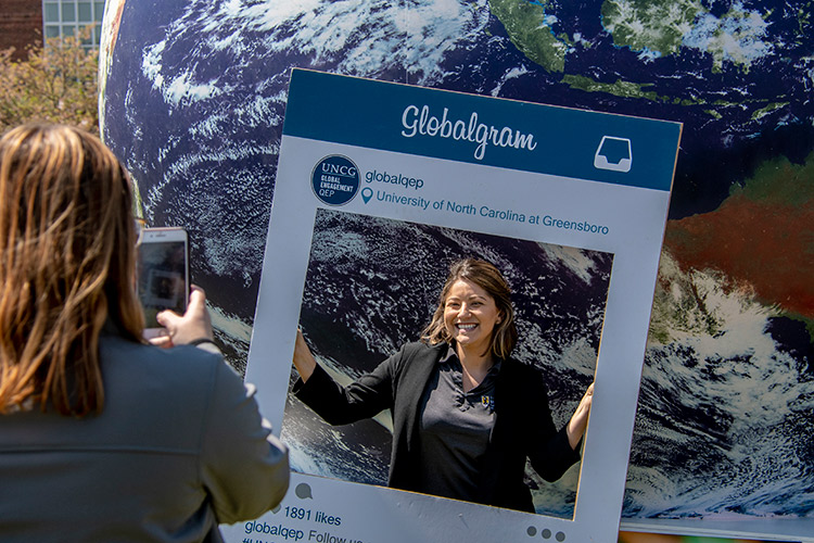 photo of woman having her photo taken with an Instagram frame
