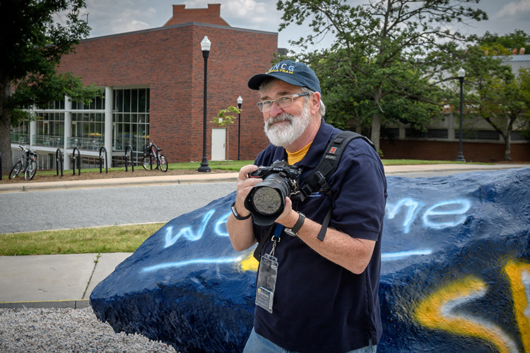 photo of Martin W. Kane, photographer, holding his camera in front of the Rawk.