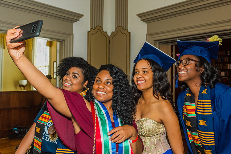 photo of 4 female graduating students taking a selfie photo