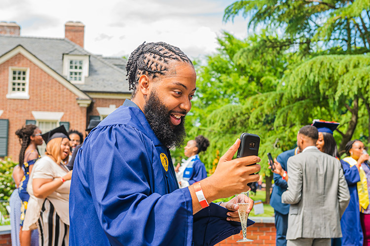 photo of male graduating student looking at his cellphone
