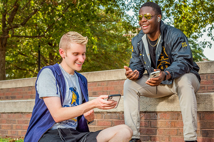 photo of 2 males in conversation holding cellphones